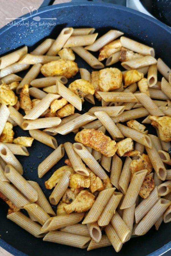 Wymieszanie makaronu z kurczakiem na patelni